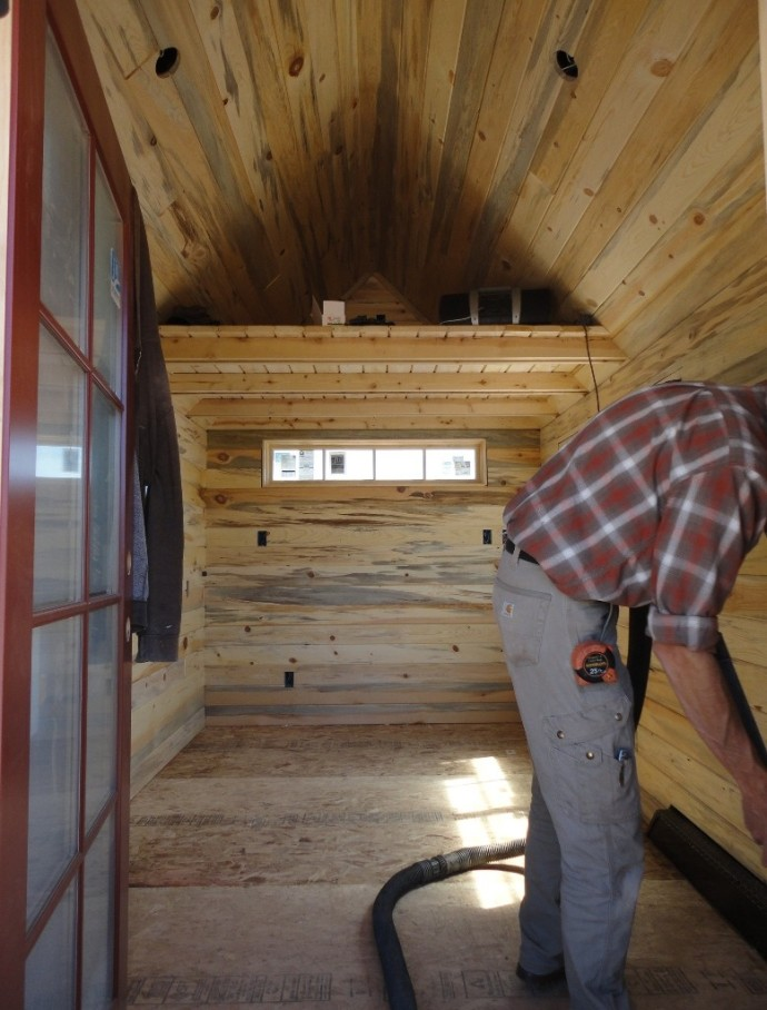 All the tongue and groove paneling is installed on the interior of the Tiny House and Shane vacuums the space in preparation for the wood flooring.