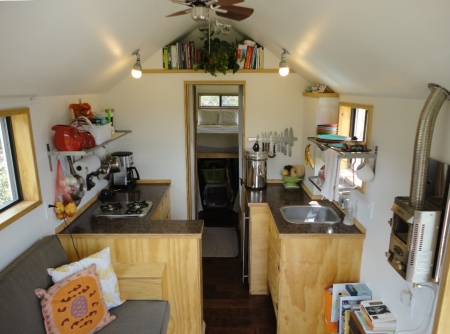 We designed our 204sf tiny house to be suitable for two occupants.  Pocket doors separate the pass-through bathroom from the bedroom in the back and the great room and kitchen in the front.    photo by Carrie Caverly